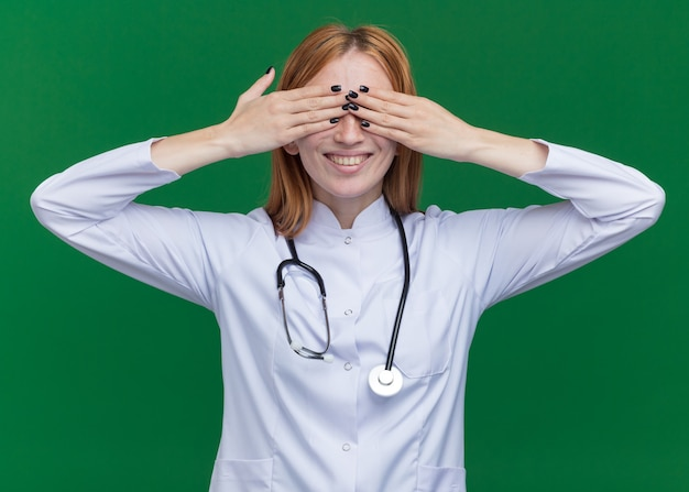 Sorridente giovane dottoressa allo zenzero che indossa un abito medico e uno stetoscopio che copre gli occhi con le mani isolate sul muro verde