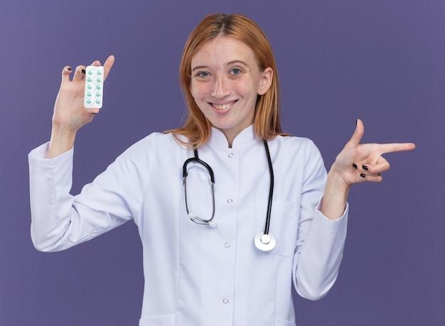 Sorridente giovane dottoressa allo zenzero che indossa abito medico e stetoscopio che mostra il pacchetto di pillole mediche alla telecamera che punta a lato isolato sulla parete viola