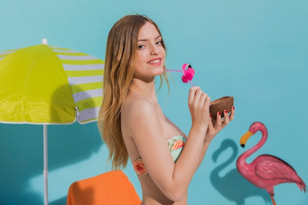 Smiling young female holding tropical cocktail in studio