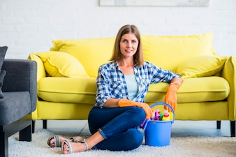 Smiling young female housekeeper sitting on carpet with cleaning equipments
