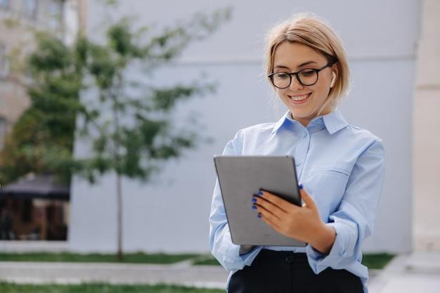 手に持っているタブレット画面を見ている眼鏡と青いシャツで若い女性の笑顔。新鮮な空気のガジェットを使用してブロンドの髪のきれいな女性。