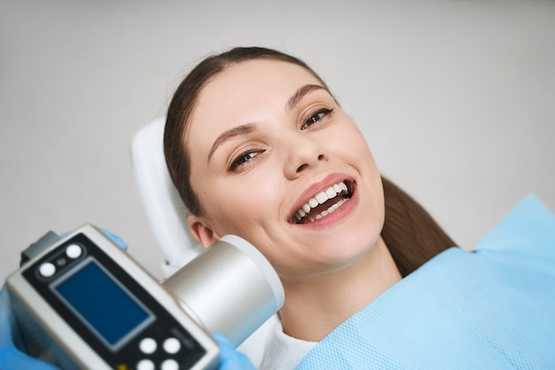 Smiling young female is lying in dental chair and being treated with special electronical gadget