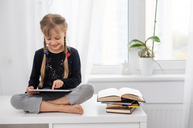 온라인 비디오를 시청하는 디지털 태블릿 패드를 사용하여 어린 여성 아이 어린이 미소 짓기