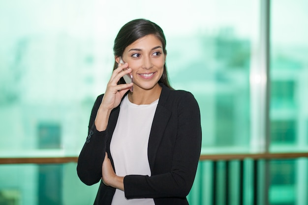 Smiling young female manager calling to client
