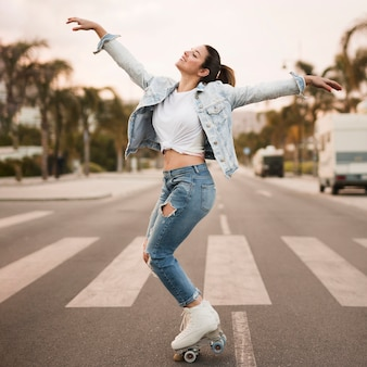 Smiling young female skater balancing on the crosswalk