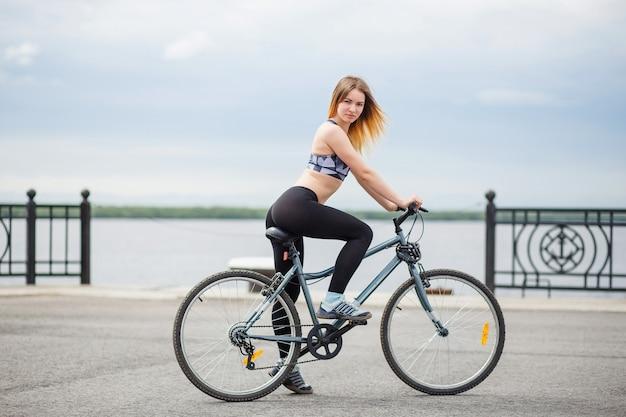 堤防に自転車で立っている笑顔の若い女性。スポーツトップとレギンスに身を包んだ女の子。