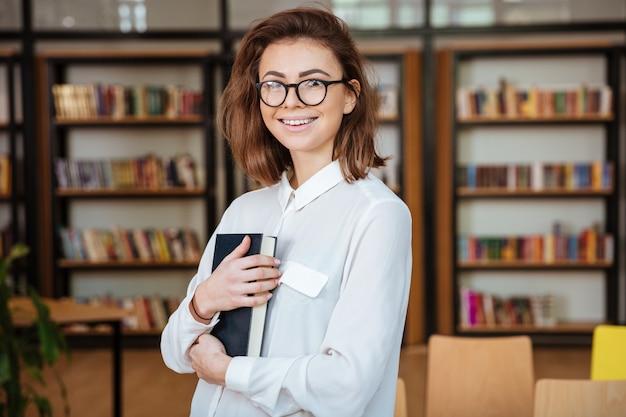 本を持って眼鏡の若い女子学生を笑顔