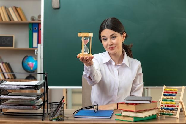 Sorridente giovane insegnante femminile che porge la clessidra seduta al tavolo con gli strumenti della scuola in classe