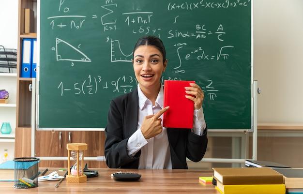 笑顔の若い女性教師は、学用品を持ってテーブルに座って、教室の本を指しています