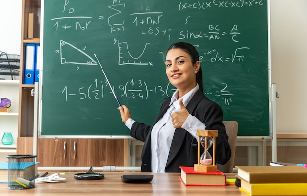 웃고 있는 젊은 여교사는 교실에서 엄지손가락을 보여주는 포인터 스틱과 함께 칠판에 학용품 포인트가 있는 탁자에 앉아 있다