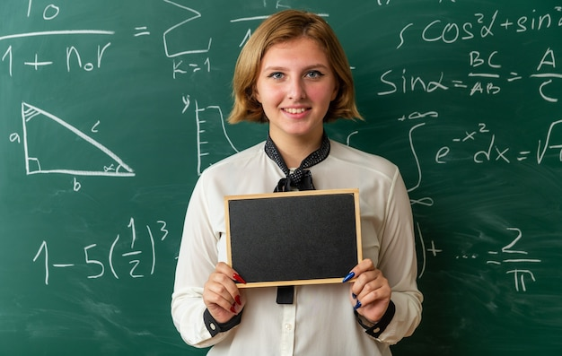 Sorridente giovane insegnante femminile in piedi davanti alla lavagna con mini lavagna in aula