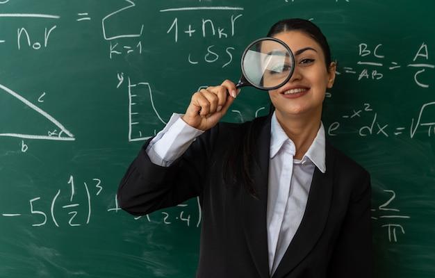 Sorridente giovane insegnante femminile in piedi davanti alla lavagna guardando la telecamera con la lente d'ingrandimento in classe