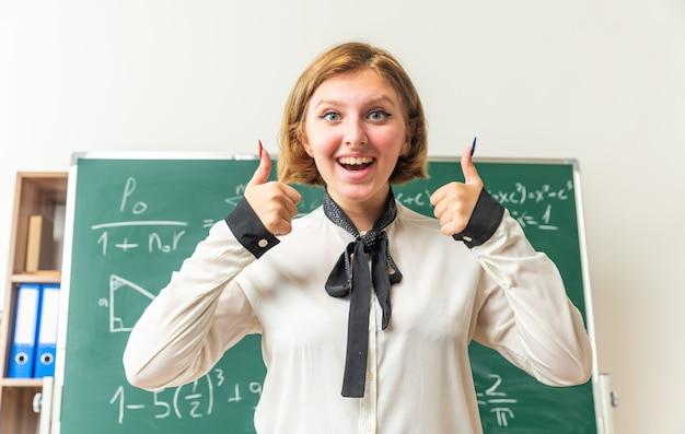 Sorridente giovane insegnante femminile in piedi davanti alla lavagna che mostra i pollici in aula