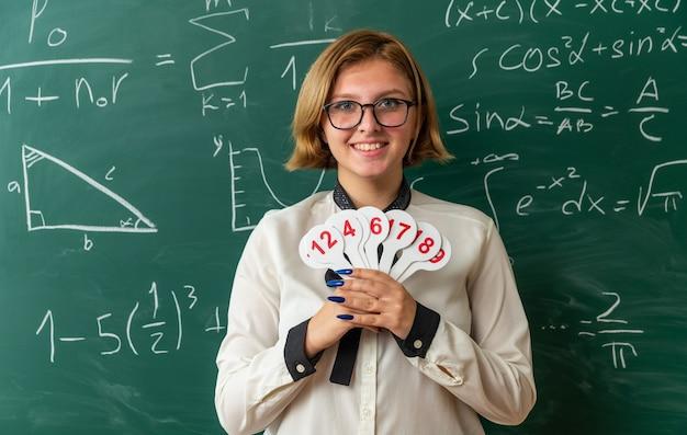 Sorridente giovane insegnante di sesso femminile con gli occhiali in piedi di fronte alla lavagna che tiene il numero di fan in aula