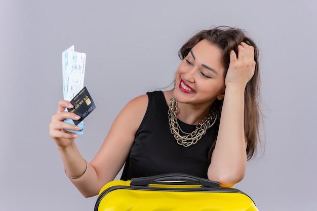 Улыбающаяся молодая женщина-путешественница в черной майке держит билеты и кладет руку на чемодан на белой стене