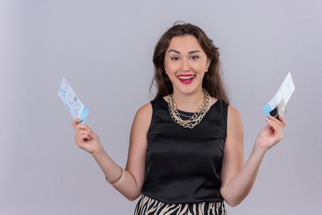 Sorridente giovane donna che indossa la maglietta nera che tiene i biglietti e la macchina di credito sul muro bianco