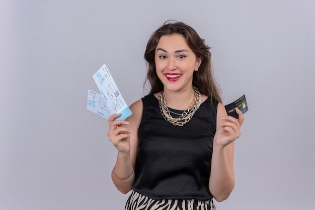 Sorridente giovane donna che indossa la maglietta nera che tiene i biglietti e la carta di credito sul muro bianco