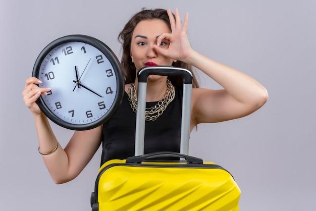 Sorridente giovane donna che indossa la maglietta nera che tiene l'orologio da parete e mostra il gesto okey sulla parete bianca
