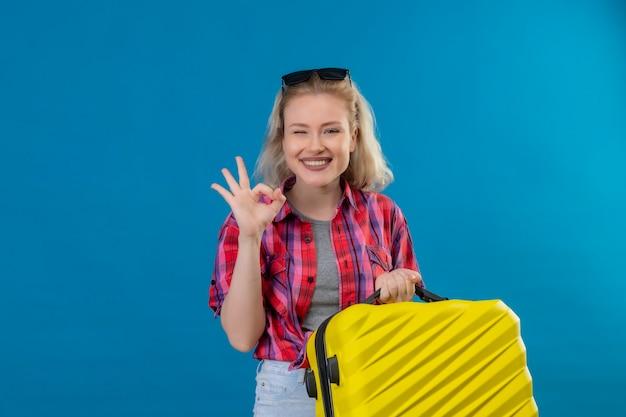 Sorridente giovane viaggiatrice che indossa la camicia rossa e occhiali sulla valigia della holding della testa che mostra okey gesto sulla parete blu isolata