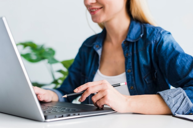 Smiling young female using laptop in workplace