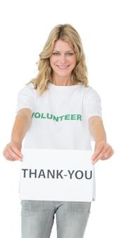 「ありがとう」紙を持っている若い女性ボランティアを笑って