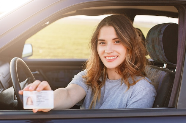 Smiling young female with pleasant appearance shows proudly her drivers license, sits in new car, being young inexperienced driver