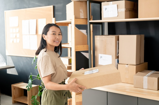 Smiling young female worker of post office or storage room carrying cardboard box with order of client for packing while looking at you