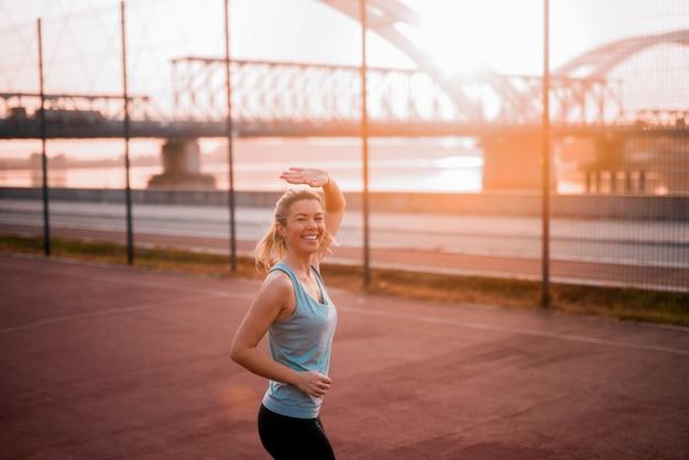 彼女の友人に手を振って早朝ジョギングで若いフィット少女の笑顔。