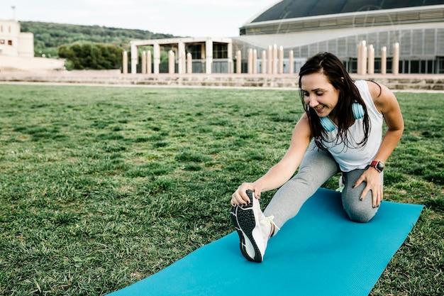 トレーニングセッションの前に公園で屋外ストレッチストレッチ若いフィット女性の笑顔