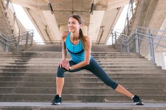 Улыбающийся молодой фитнес женщина бегун протягивая ноги перед запуском на лестнице
