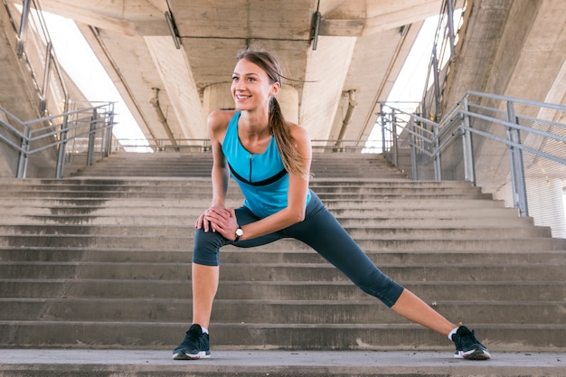 Smiling young fitness female runner stretching her legs before running on staircase