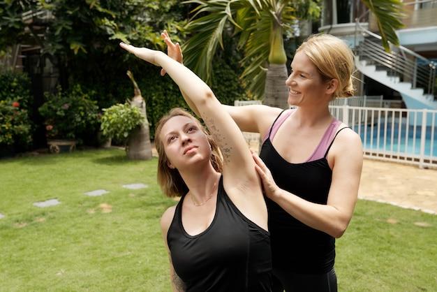 웃는 젊은 피트니스 트레이너가 젊은 여성에게 팔을 머리 위로 들고 옆으로 구부리는 방법을 설명합니다.