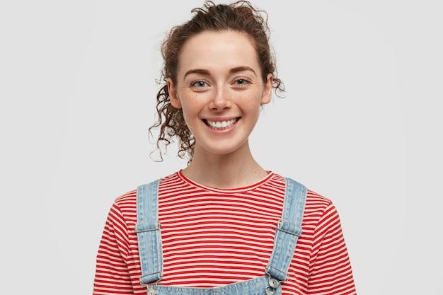 ポジティブな表情で笑顔の若いそばかすのあるヨーロッパの女性は、陽気な表情をしており、デニムのオーバーオールと赤い縞模様のセーターを着て、気分が良く、白い壁に隔離されています