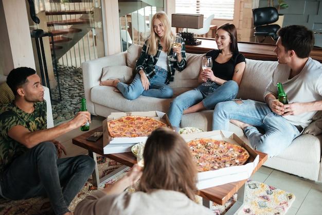 Улыбающиеся молодые друзья едят пиццу и разговаривают дома