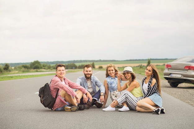 農村の道路に座っている若い友達を笑顔