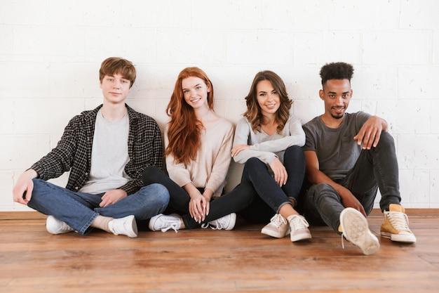 Улыбающиеся молодые друзья студентов над белой стеной