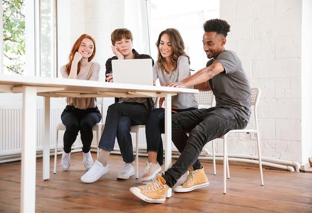 Улыбающиеся молодые друзья студентов с помощью портативного компьютера.