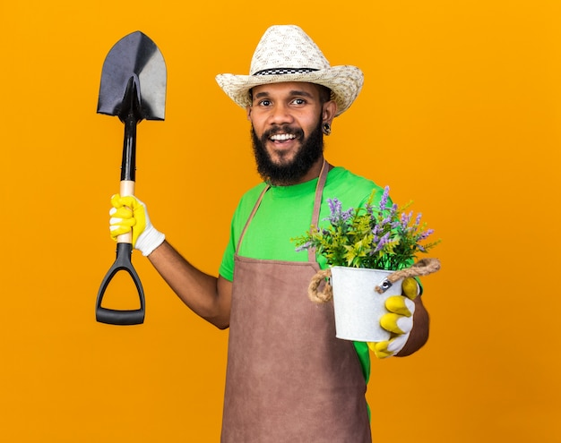 Smiling young gardener afro-american guy wearing gardening hat and gloves holding spade with flower in flowerpot isolated on orange wall