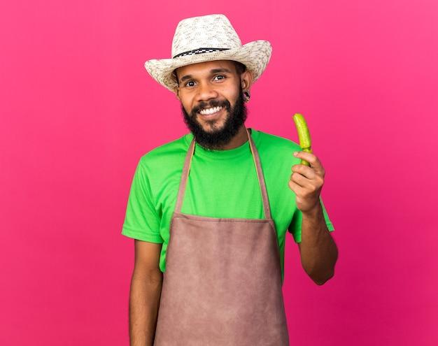웃고 있는 젊은 정원사 아프리카계 미국인 남자가 분홍색 벽에 격리된 부러진 후추를 들고 원예용 모자를 쓰고 있다