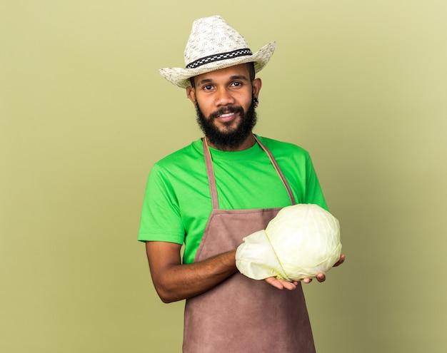Sorridente giovane giardiniere afro-americano che indossa un cappello da giardinaggio che tiene cavolo isolato su una parete verde oliva