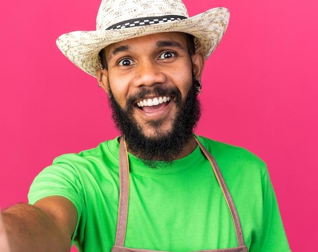 カメラを保持しているガーデニングの帽子をかぶっている若い庭師のアフリカ系アメリカ人の男を笑顔
