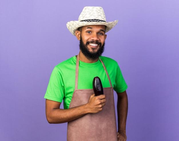 Sorridente giovane giardiniere afro-americano che indossa cappello da giardinaggio tenendo melanzane isolate sulla parete blu