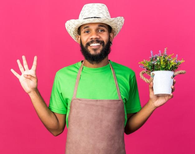 웃고 있는 젊은 정원사 아프리카계 미국인 남자가 꽃 냄비에 꽃을 들고 정원용 모자를 쓰고 분홍색 벽에 격리된 4개를 보여줍니다.
