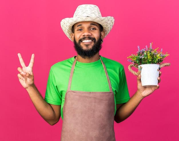 平和のジェスチャーを示す植木鉢に花を保持しているガーデニングの帽子をかぶっている若い庭師のアフリカ系アメリカ人の男を笑顔