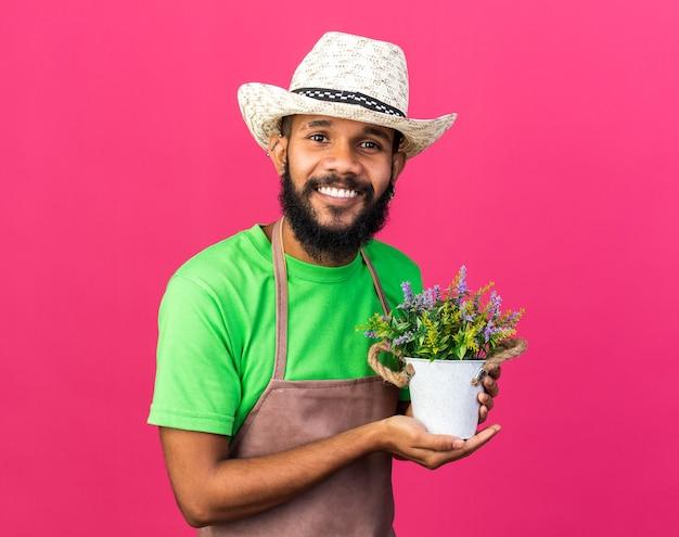 植木鉢に花を保持しているガーデニングの帽子をかぶっている若い庭師のアフリカ系アメリカ人の男を笑顔