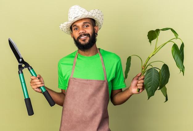 Sorridente giovane giardiniere afro-americano che indossa cappello da giardinaggio che tiene pianta con forbici isolate su muro verde oliva