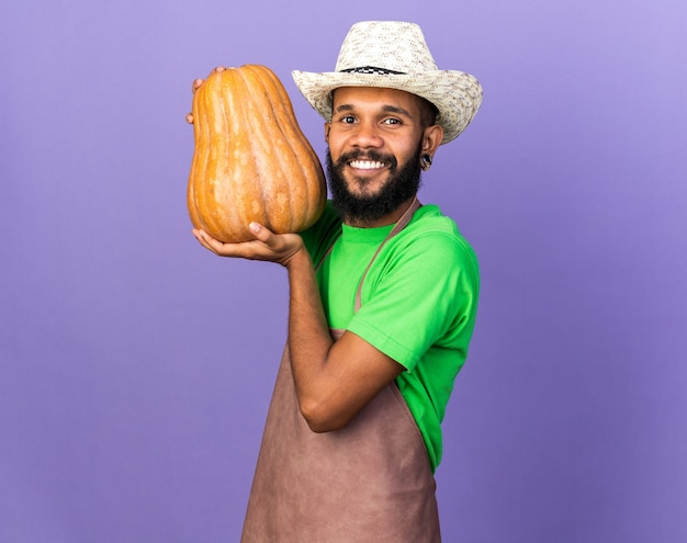 Smiling young gardener afro-american guy wearing gardening hat holding pumpkin isolated on blue wall