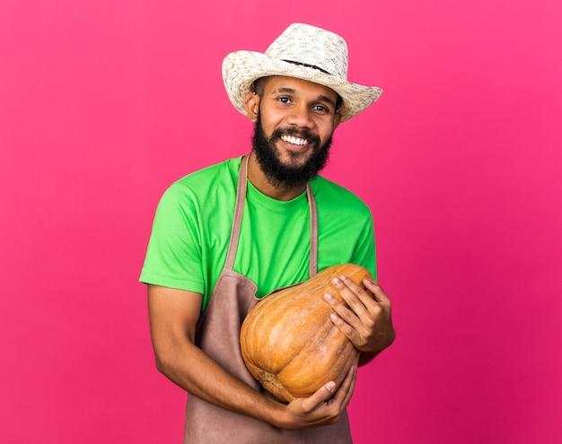 Sorridente giovane giardiniere afroamericano che indossa un cappello da giardinaggio che tiene in mano una zucca isolata sul muro rosa