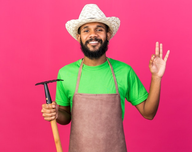 Smiling young gardener afro-american guy wearing gardening hat holding rake showing okay gesture isolated on pink wall