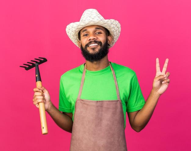 平和のジェスチャーを示す熊手を保持しているガーデニングの帽子をかぶっている若い庭師のアフリカ系アメリカ人の男を笑顔